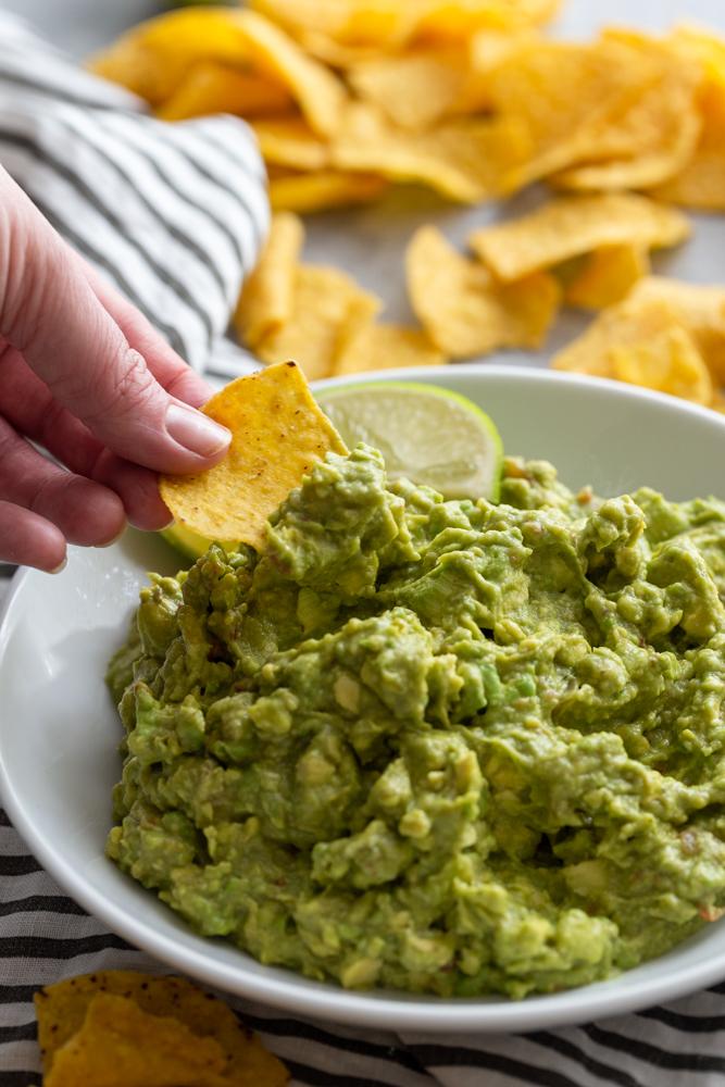 Hand dipping tortilla chip into guacamole