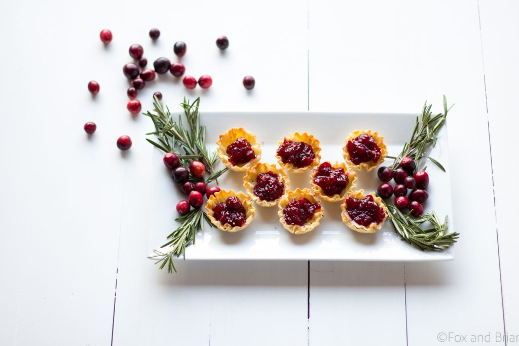 Cranberry Brie Mini Tarts. These easy, 3 ingredients appetizers are perfect for any holiday party that you will be hosting or attending. Buttery brie and sweet tart cranberry sauce in a crispy shell make adorable bite sized appetizers.