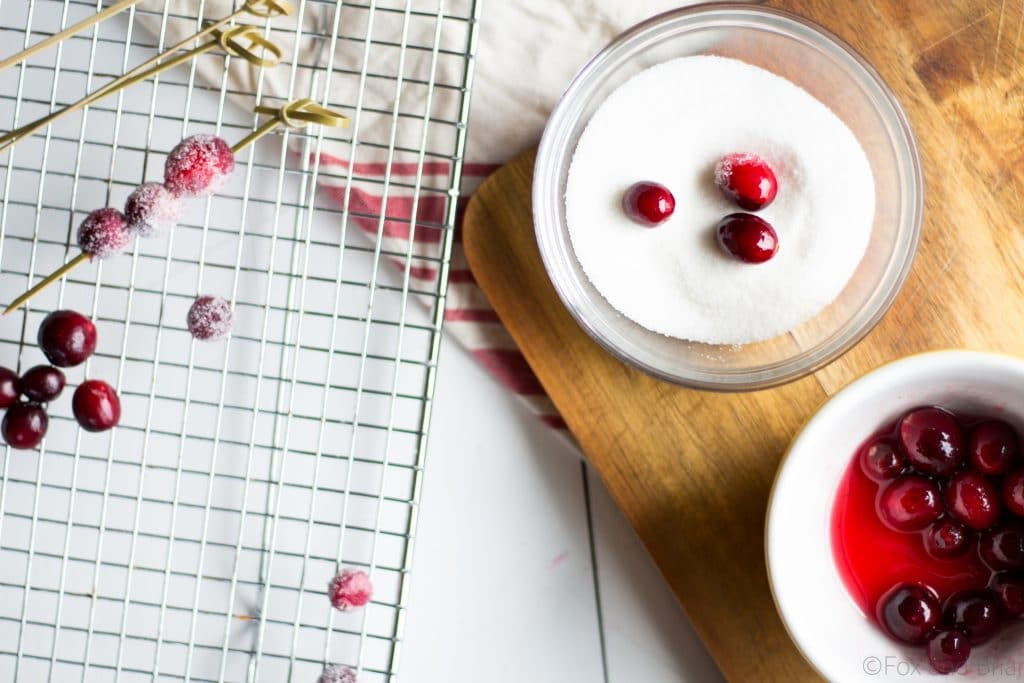Homemade cranberry orange syrup takes this standby cocktail up a notch. Cranberry Juice, Grand Marnier, Orange juice and cranberry orange syrup combine to make a festive winter cocktail. There is a non-alcoholic mocktail version as well!