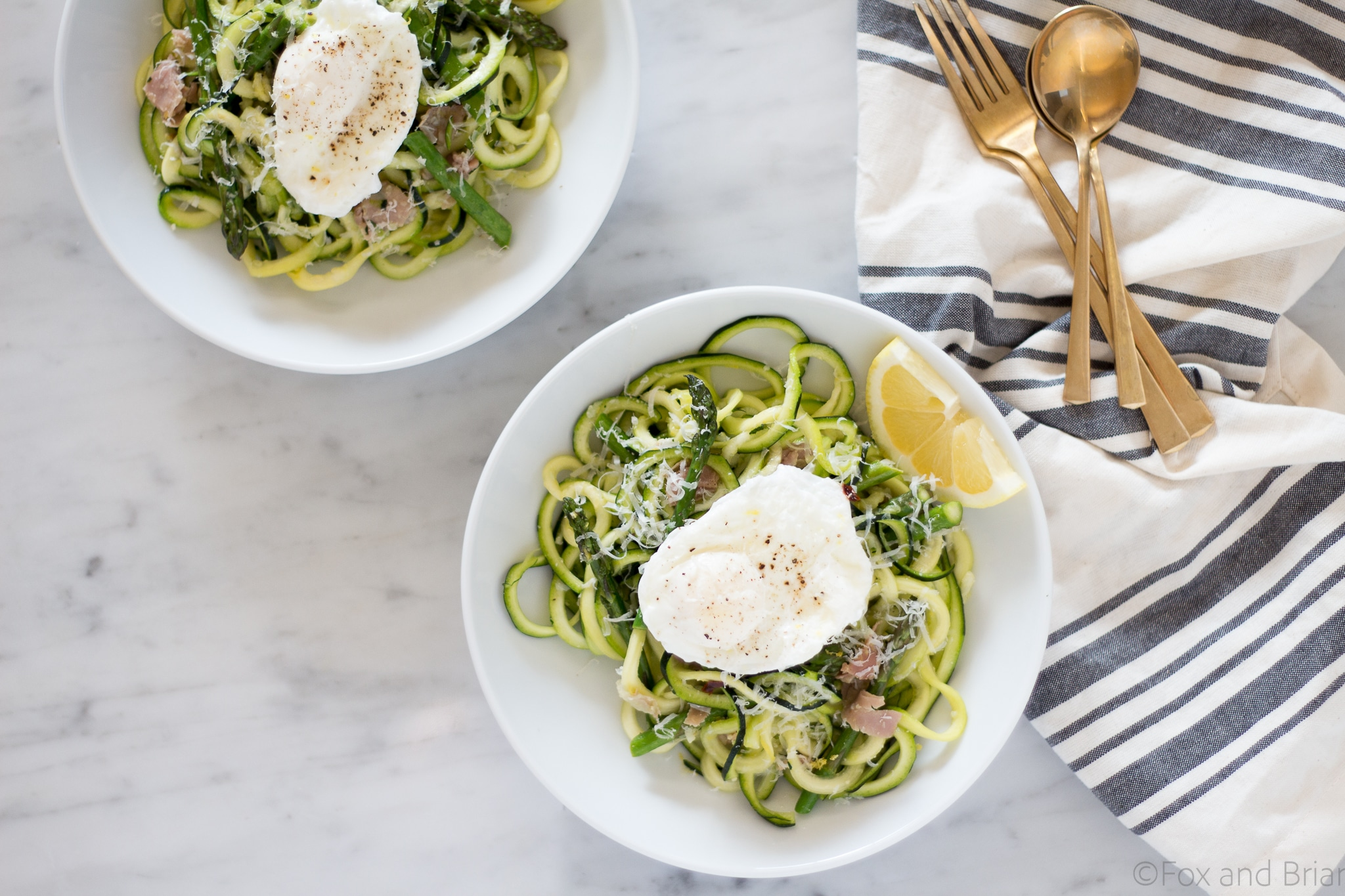 Zoodles (zuchinni noodles) quick cooked with asparagus, prosciutto, parmesan cheese, lemon and white wine all topped with a poached egg make a quick and light spring meal.