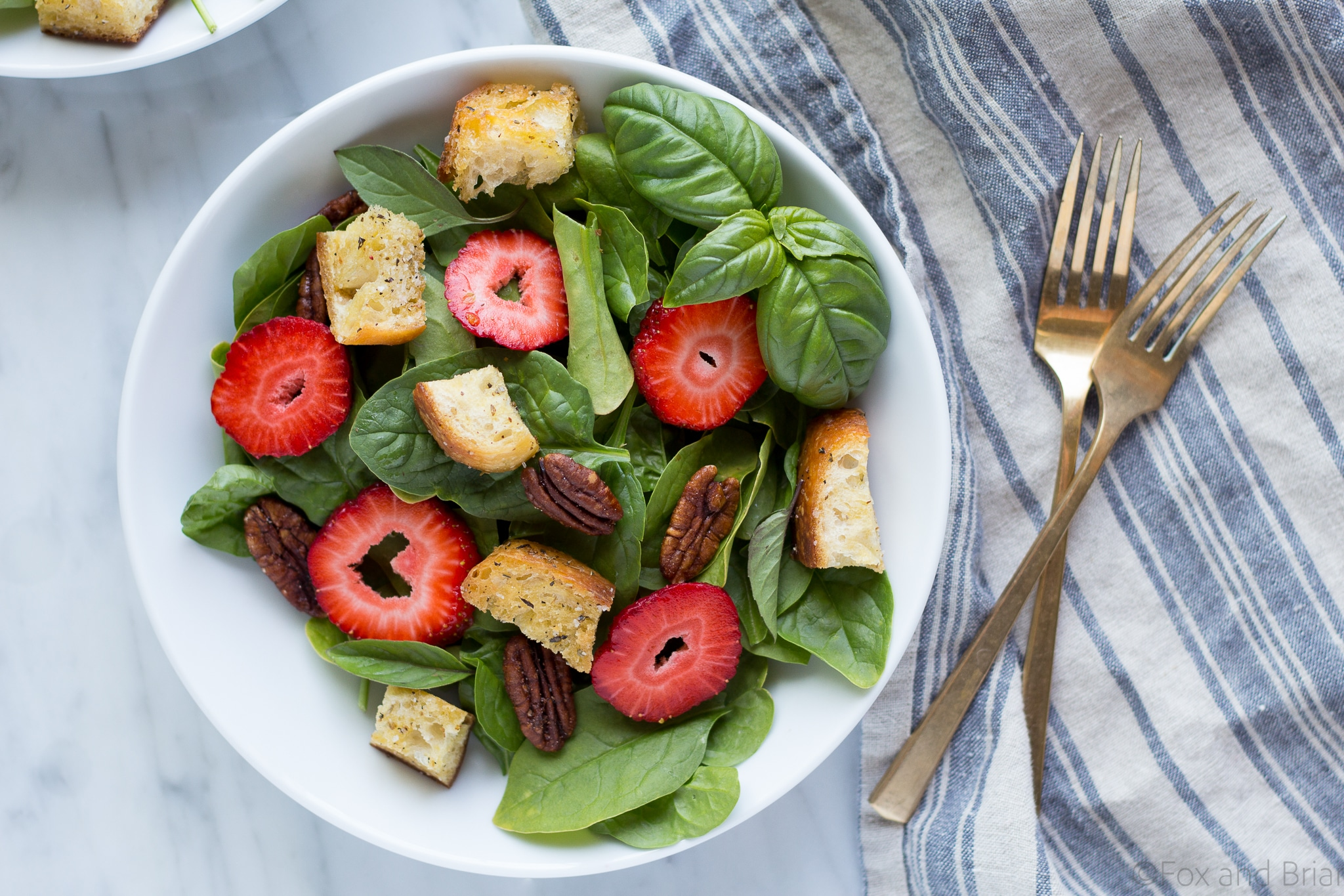 This Strawberry Basil Pecan Salad with Goat Cheese Dressing is a sweet and tangy summer salad bursting with fresh flavors and homemade croutons.