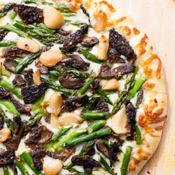 This Asparagus and Morel Pizza with Garlic Confit is the perfect way to use your spring produce! Garlicky and cheesey, packed full of flavor and vegetarian!