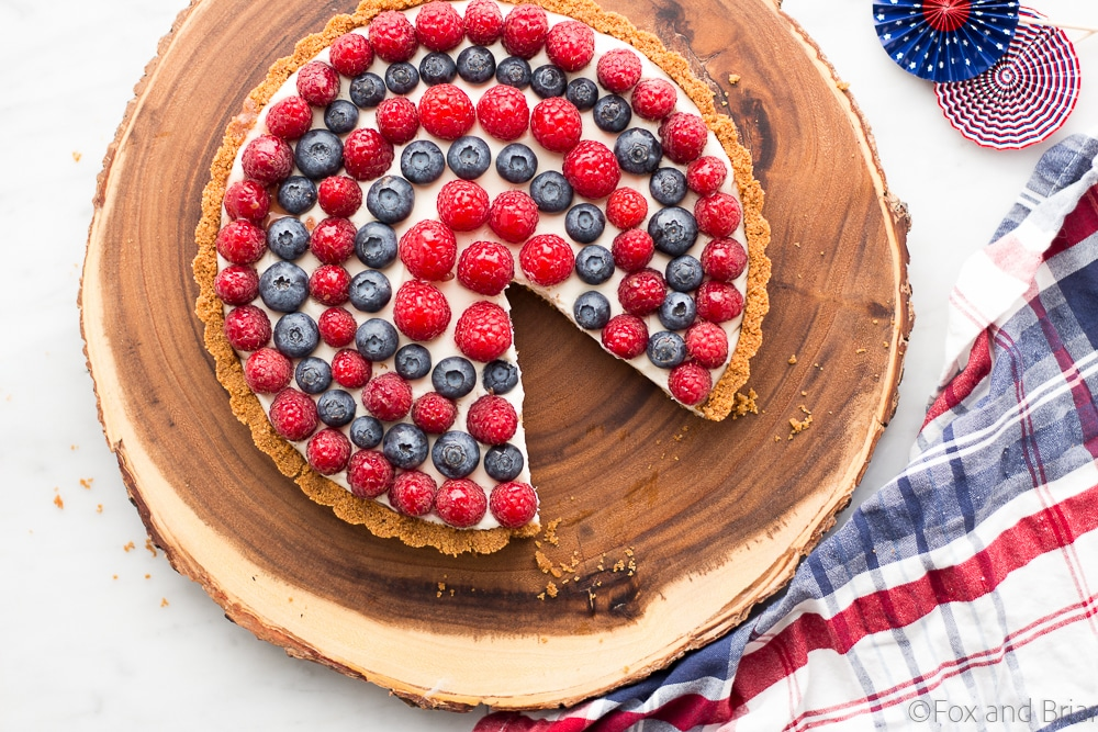 This Red, White and Blueberry Tart is a fresh berry tart perfect for 4th of July or any summer day! Fresh berries, a sweet creamy filling and a graham cracker crust make this simple and delicious tart a total winner!
