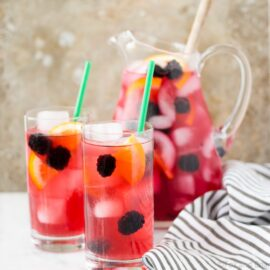 This Berry Sangria Iced Tea is a take on the Starbucks drink! Herbal iced tea mixed with a berry orange syrup, apple juice and blackberries! So refreshing for a hot summer day.