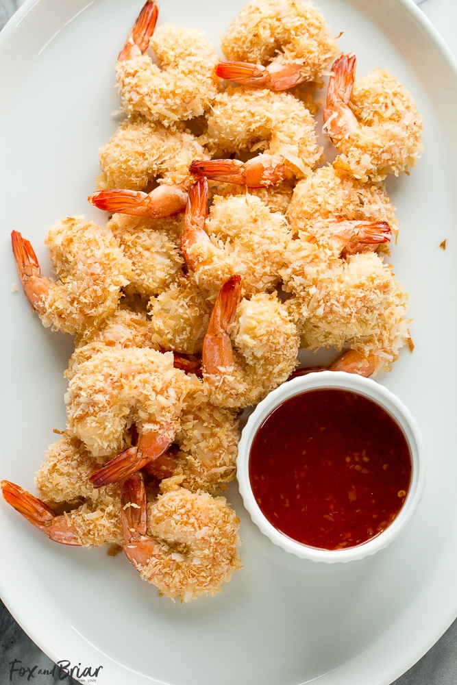 These Baked Coconut Shrimp are golden, crispy and full of flavor. You won't even need a dipping sauce! These are the BEST baked coconut shrimp I have ever made! | How to make coconut shrimp | Baked coconut shrimp | skinny coconut shrimp |