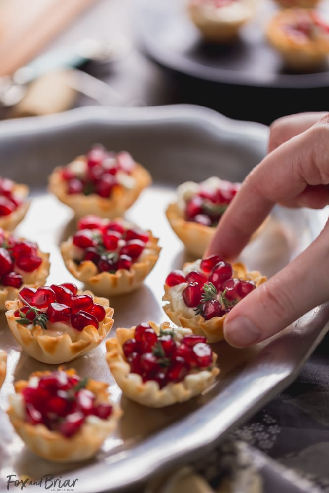 These Pomegranate Goat Cheese Bites with Honey and Thyme are an easy party appetizer that is sure to impress your guests! | easy party appetizer | phyllo bite recipe | Phyllo dough recipe | mini phyllo shells appetizers | phyllo dough hors d'oeuvres recipes | finger foods | holiday appetizer recipe | elegant party appetizer | girls night | apps | new years eve party recipe | thanksgiving appetizer |
