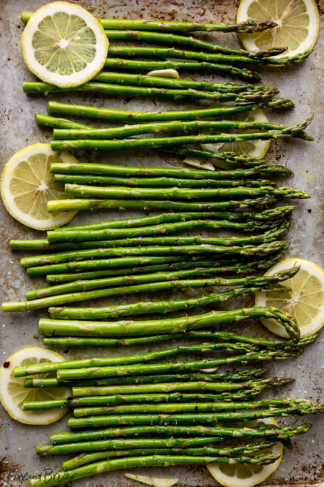 Asparagus spears on a sheet pan with lemon slices