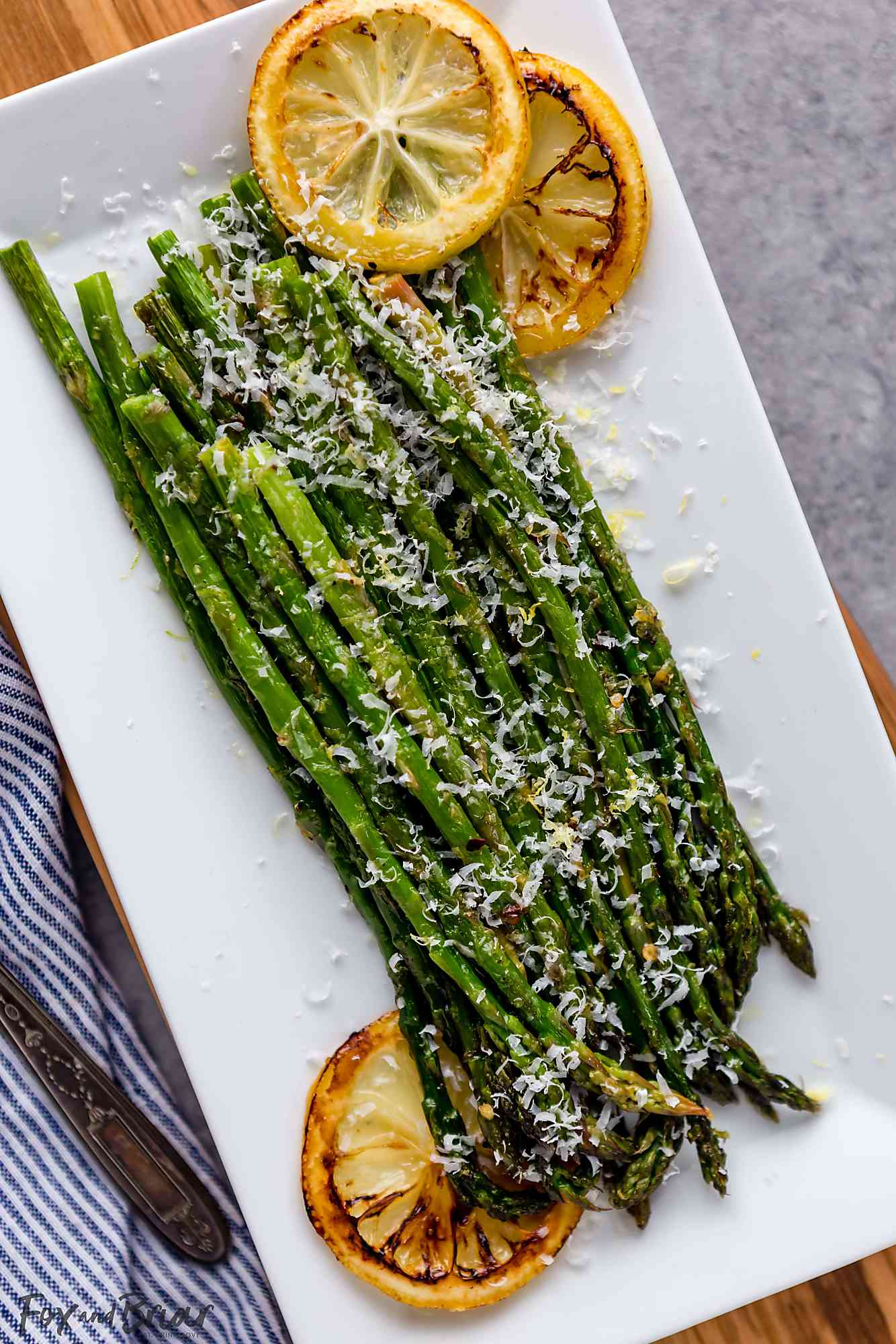 Roasted asparagus on a plate with lemon slices