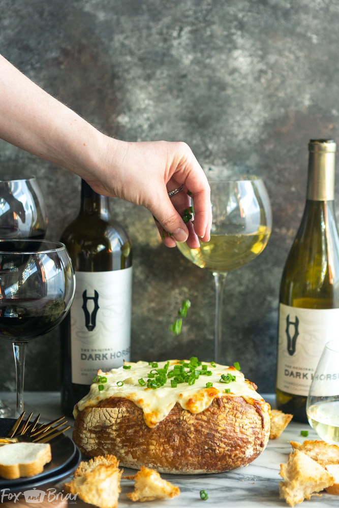 #ad This creamy and cheesy Baked Crab Artichoke Dip in a Bread Bowl will be a hit on game day! A little @darkhorsewine Chardonnay in the dip adds a complex flavor for a winning appetizer. | Dip recipe | party appetizers | crab recipes | Crab artichoke dip | Dip in a bread bowl