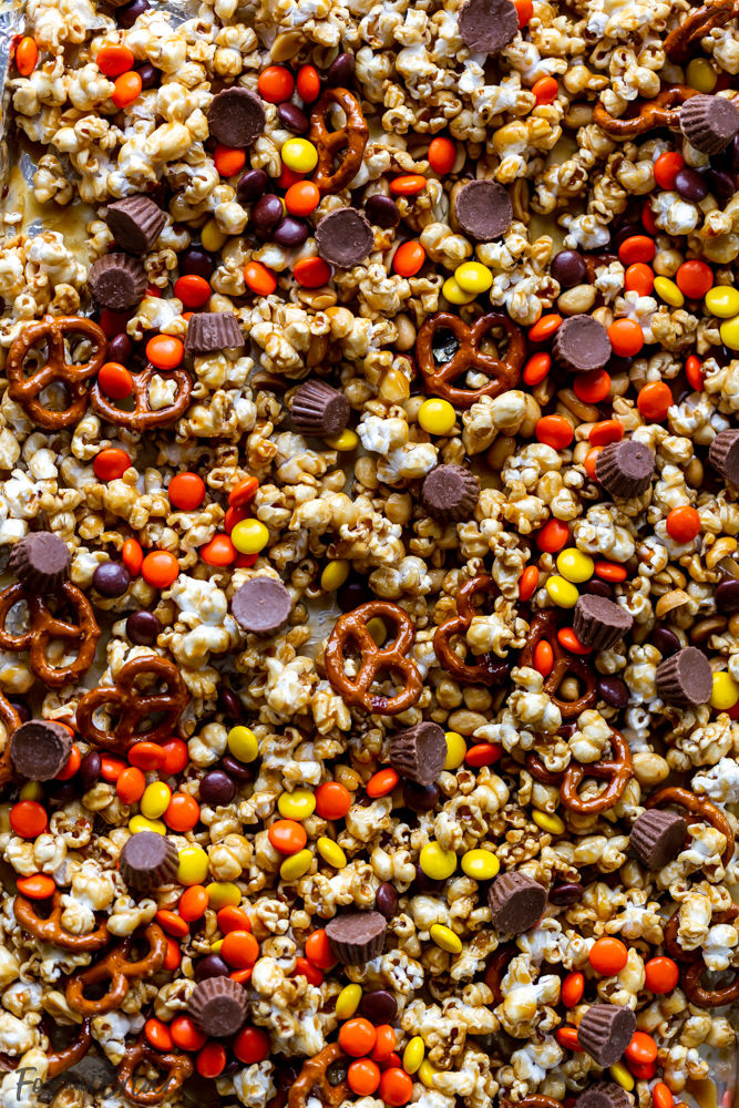 This Chocolate Peanut Butter Sweet and Salty Popcorn Snack Mix is perfect to serve at your next game day party!  Keep them coming back for more with popcorn mixed with Reese's Pieces, Reese's Peanut Butter Cups Minis , pretzels and peanuts, all mixed together with caramel. #ad @krogerco @reeses | Popcorn recipes | popcorn ideas | sweet poporn recipe | caramel corn | peanut butter chocolate