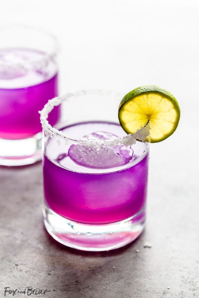 butterfly pea flower margarita with salted rim and slice of lime