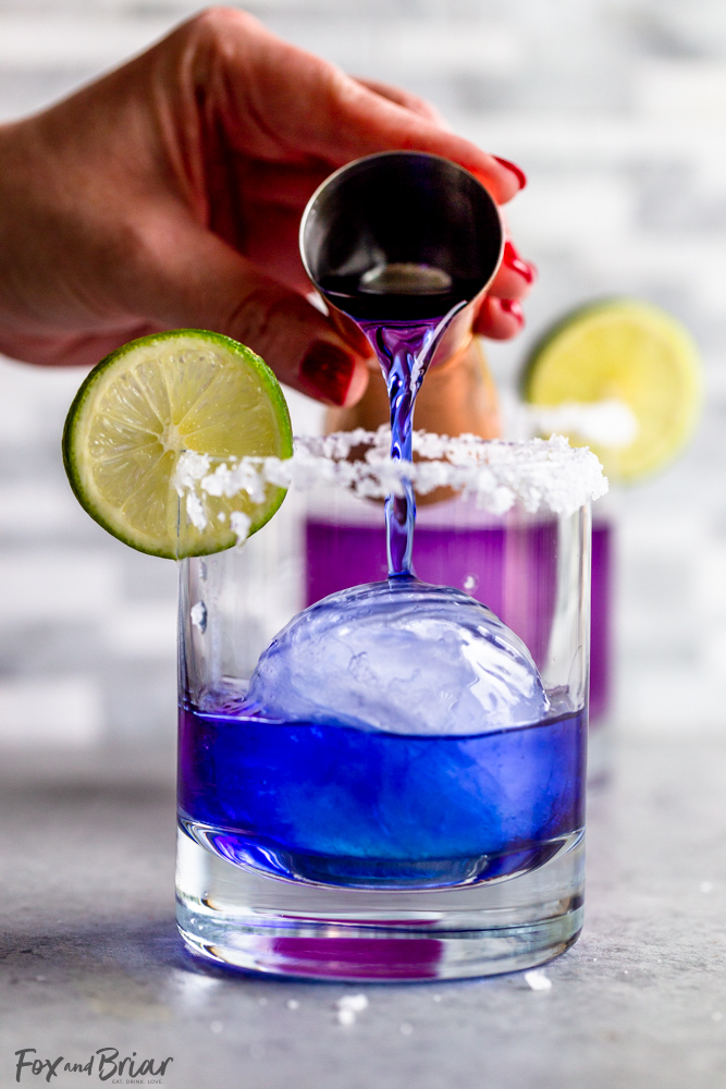 pouring blue tequila into a glass with ice