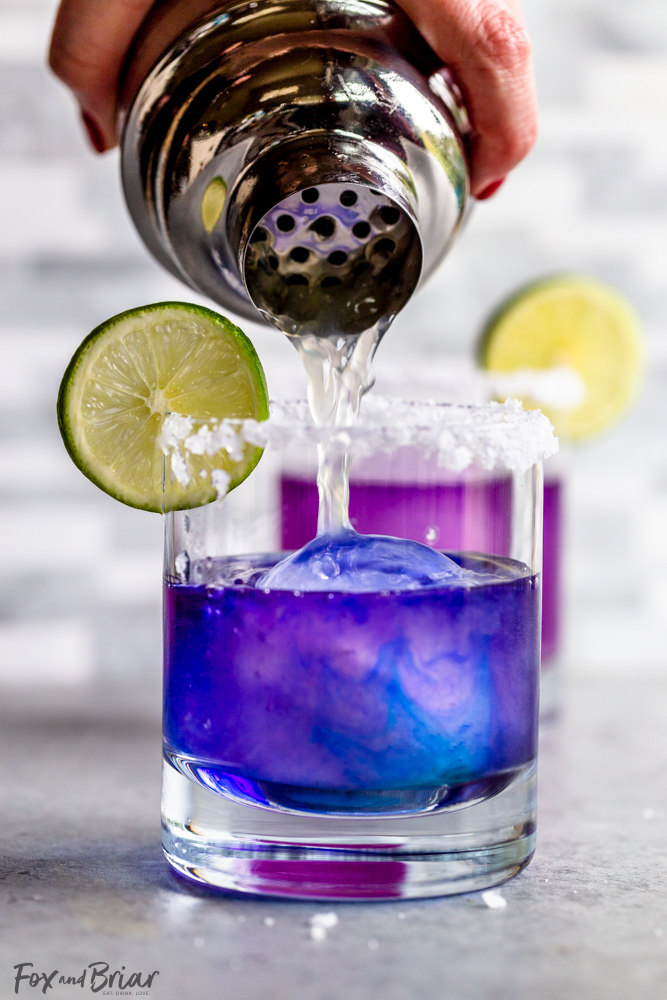 Cocktail shaker pouring lime juice into blue margarita as it turns purple