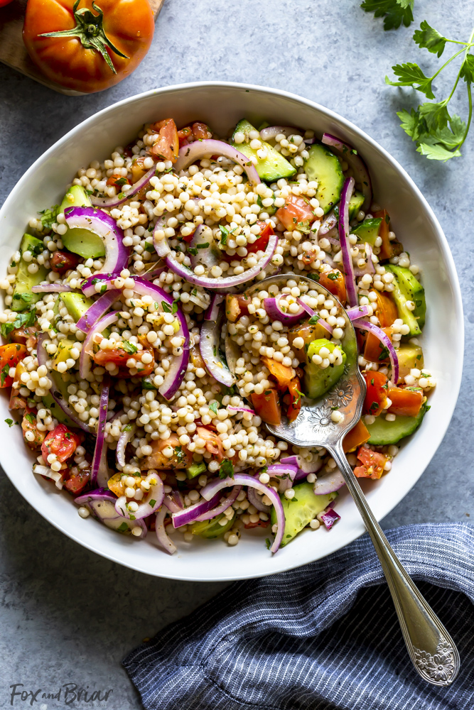 Israeli couscous salad in a white bowl with a serving spoon
