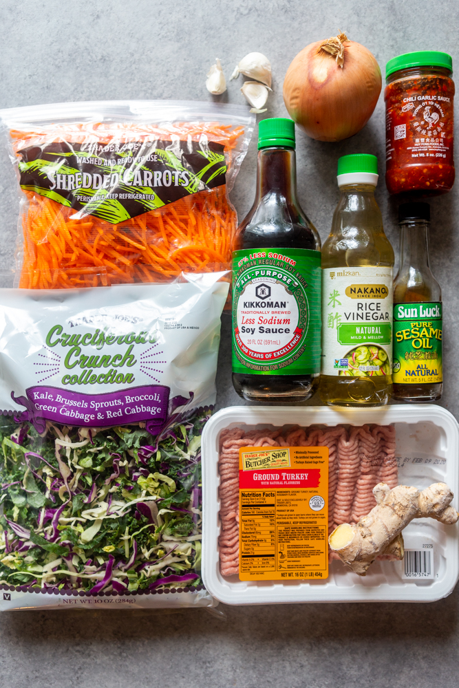 ingredients for eggroll in a bowl - carrots, onion, garlic, chicli garlic sauce, cruciferous crunch, low sodium soy sauce, rice vinegar, sesame oil, ground turkey, ginger