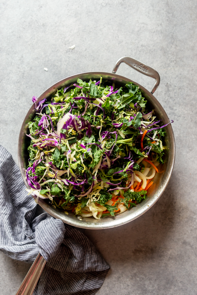 frying pan with grated carrots and green mix