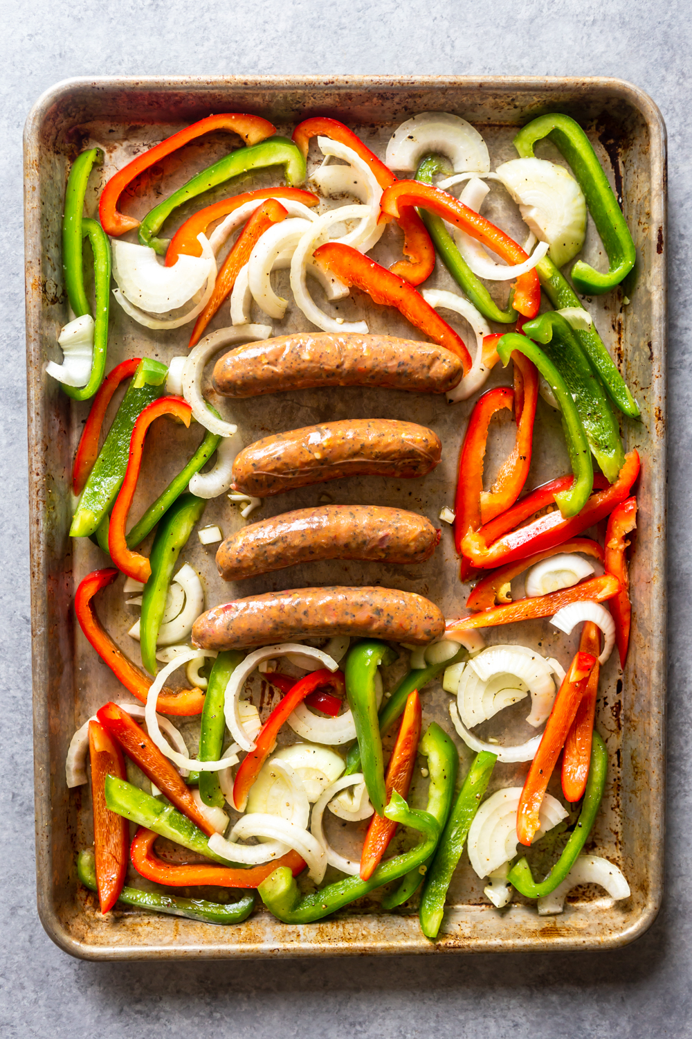 Raw peppers, onions and sausages on a sheet pan before going into the oven.