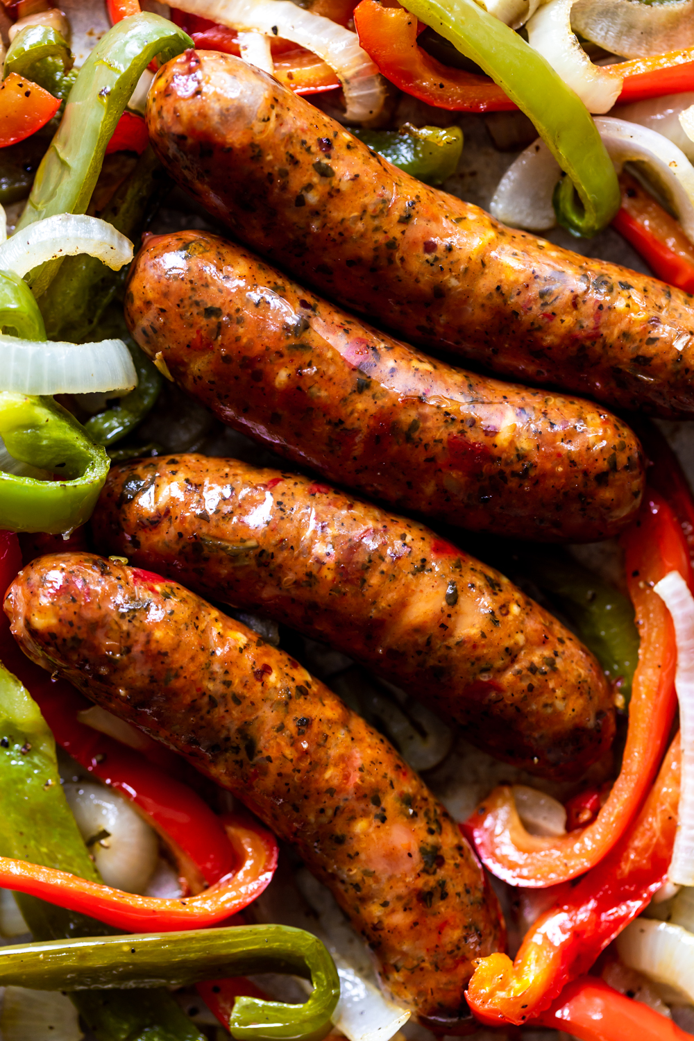 Cooked sausages with bell peppers and onions