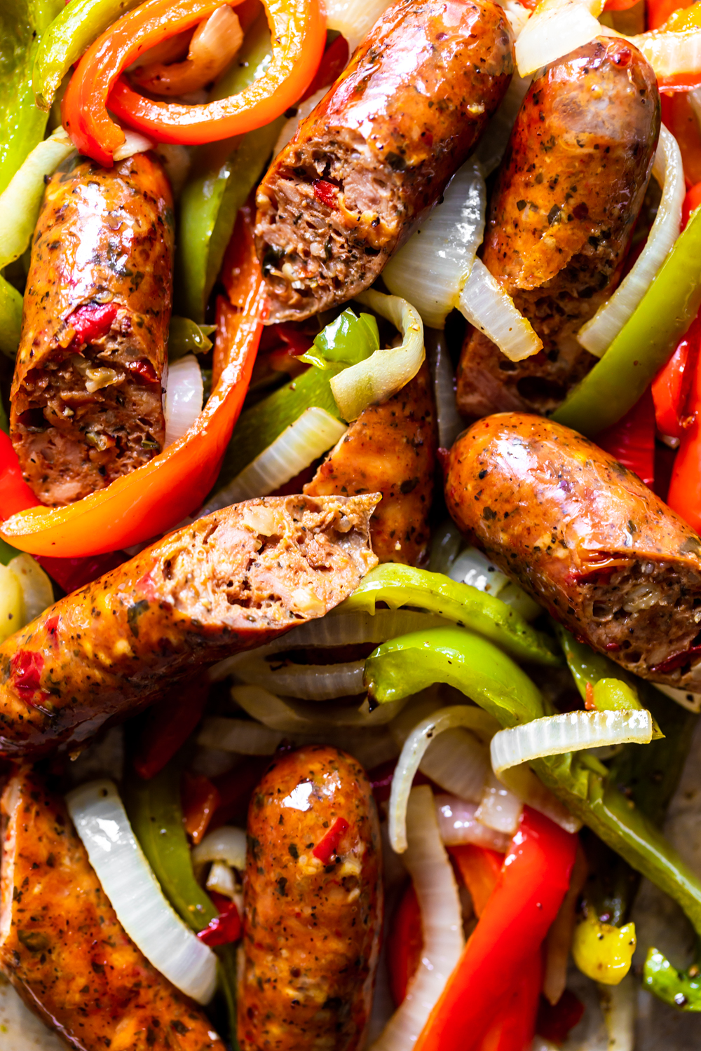 close up of sausages on a bed of peppers and onions