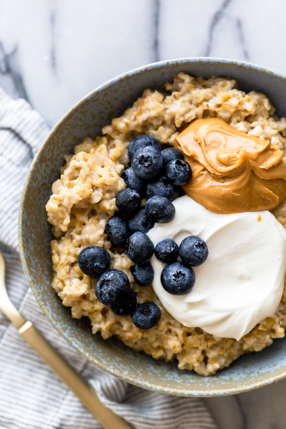 Oatmeal topped with yogurt, peanut butter and blueberries in a light blue bowl with a gold spoon