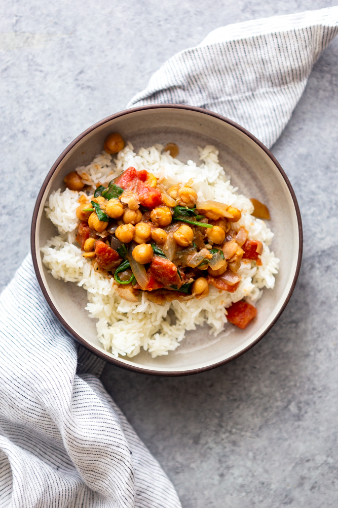 Coconut chickpea curry in a bowl with a blue and white striped napkin