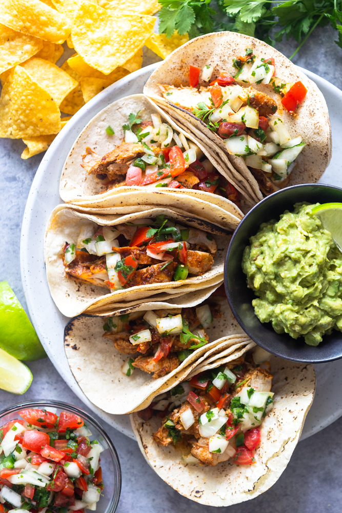 chicli lime chicken tacos on a plate surrounded by tortilla chips and pico de gallo