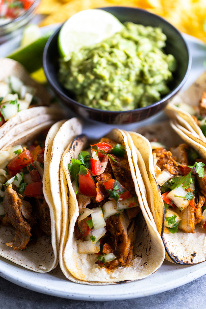 Chili lime chicken tacos on a white plate with a small dish of guacamole