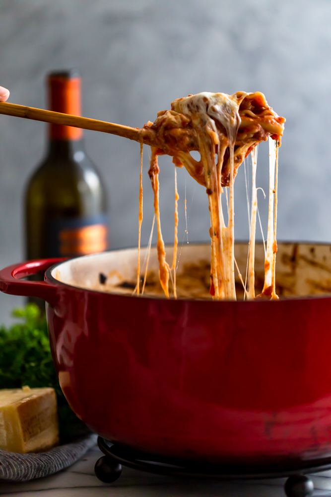 Cheesy lasagna being served from a red dutch oven