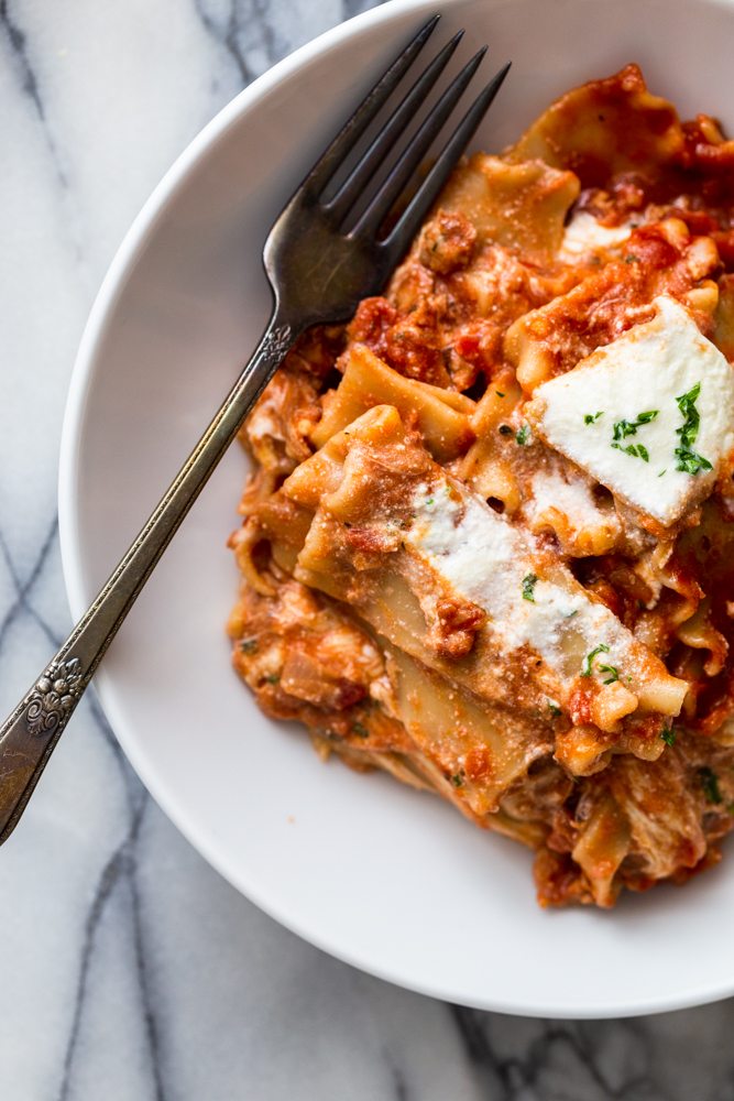 White bowl on marble background with lasagna and a fork