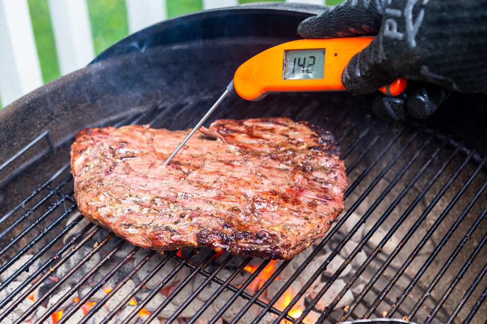 Flank Steak on a charcoal grill with a probe thermometer showing 142 degrees F