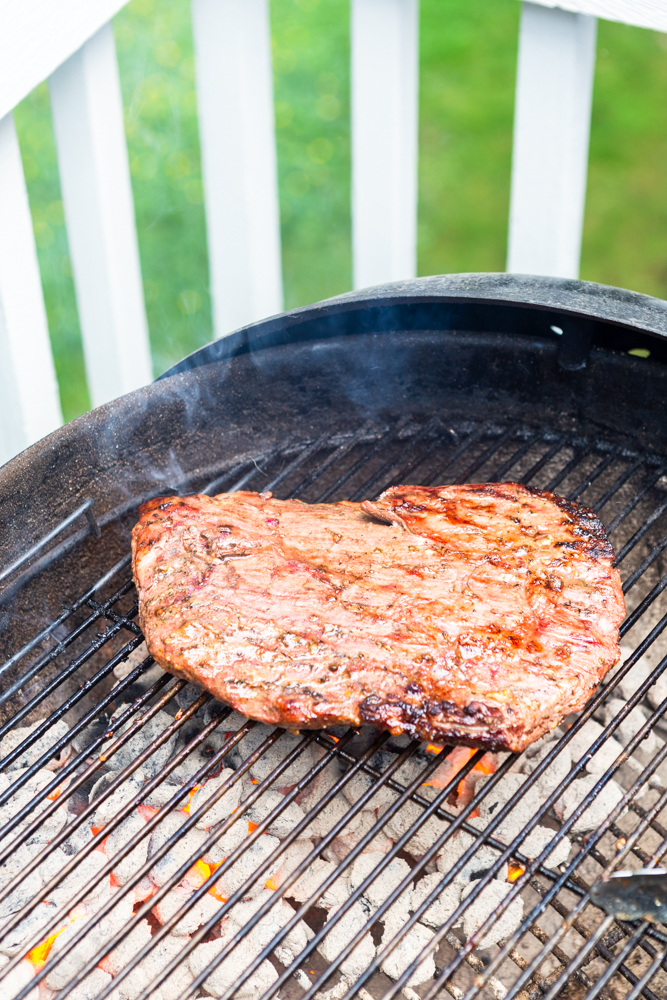 Flank steak being cooked on a charcoal grill outdoors