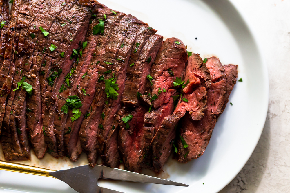 Sliced grilled flank steak on a white platter