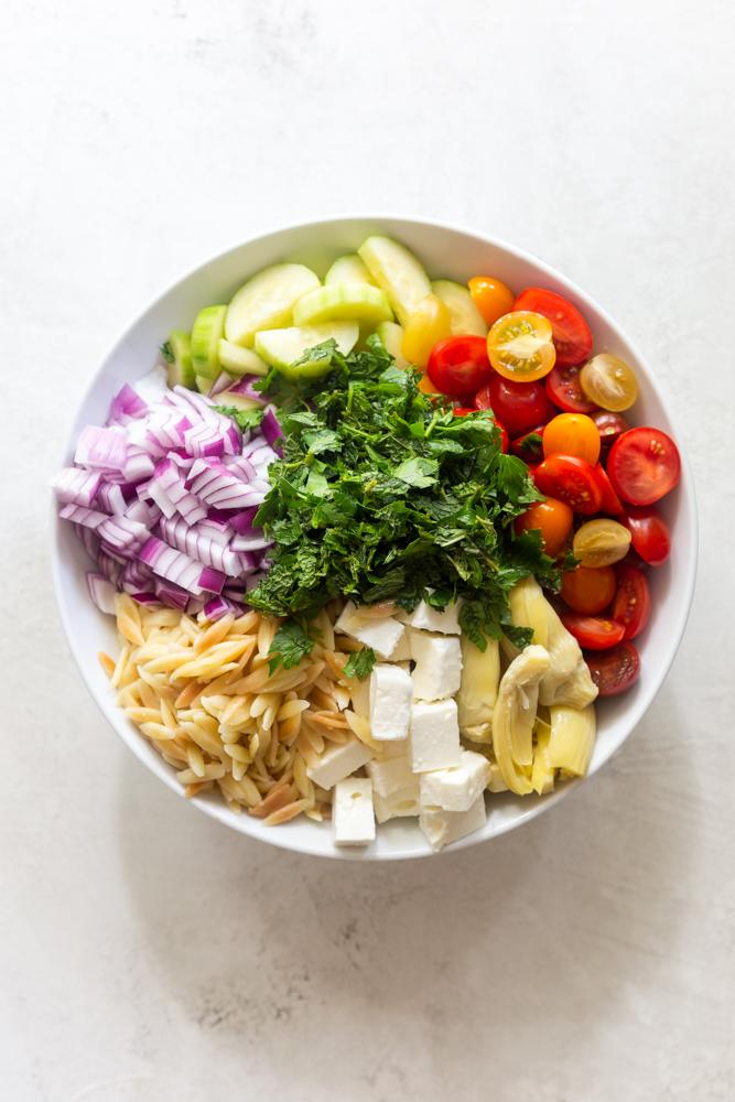 Ingredients for Mediterranean Pasta Salad - orzo, feta, artichoke, tomatoes, cucumbers, onion, herbs