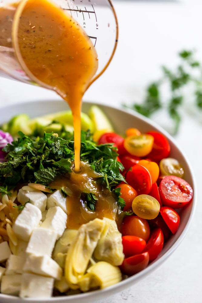 Lemon dressing pouring onto orzo salad
