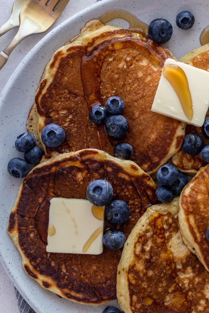 Pfannkuchen auf einem Teller mit Butter, Blaubeeren und Sirup