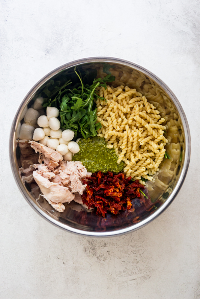 Ingredients for chicken pesto pasta salad - cooked pasta, arugula, mozzarella balls, cooked chicken, sun dried tomatoes, pesto - together in a large stainless steel bowl