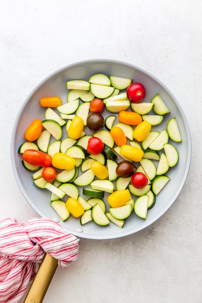 rohe Zucchini und Tomaten vor dem Kochen in einer Pfanne