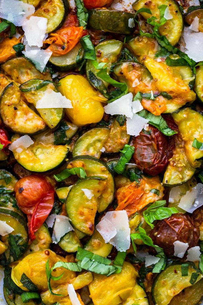 Nahaufnahme von sautierten Zucchini und Kirschtomaten mit Basilikum und Parmesan