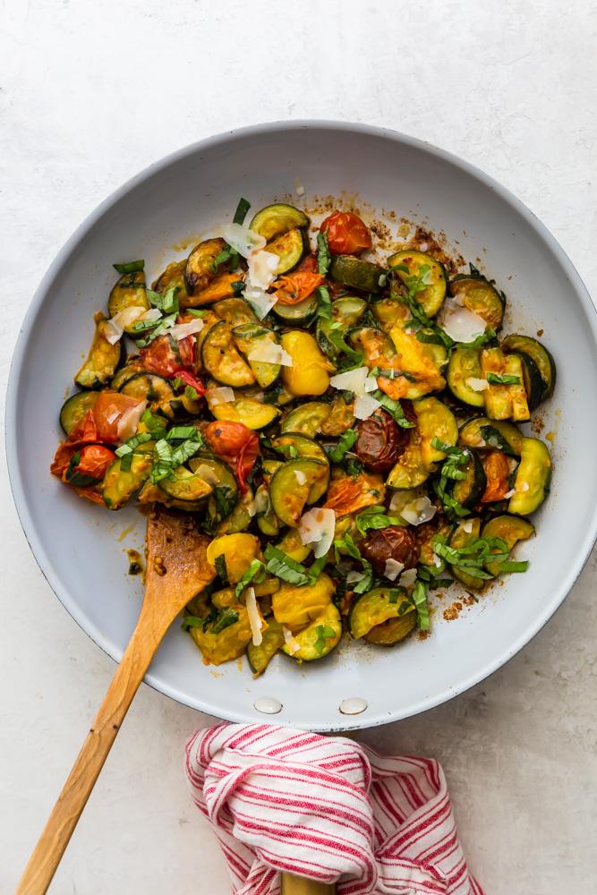Sautierte Zucchini und Kirschtomaten in einer Pfanne mit einem Holzlöffel