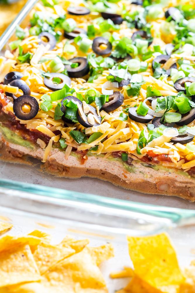 Nahaufnahme von sieben Schicht Dip zeigt die Schichten - Bohnen, Sauerrahm, Guacamole, Salsa, Käse, Oliven, Frühlingszwiebeln und Koriander.