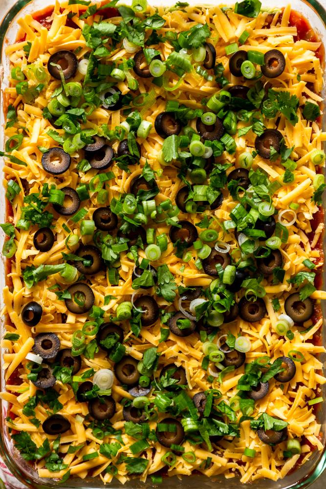 Nahaufnahme von 7-Schicht-Dip mit Käse, Oliven, Frühlingszwiebeln und Koriander oben drauf.